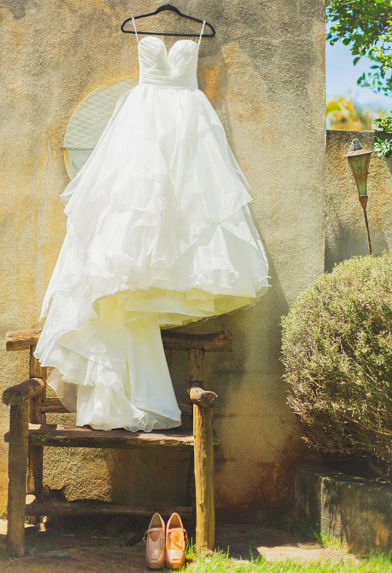 Beautiful Romantic wedding dress hung in Hawaii with pink bridal shoes
