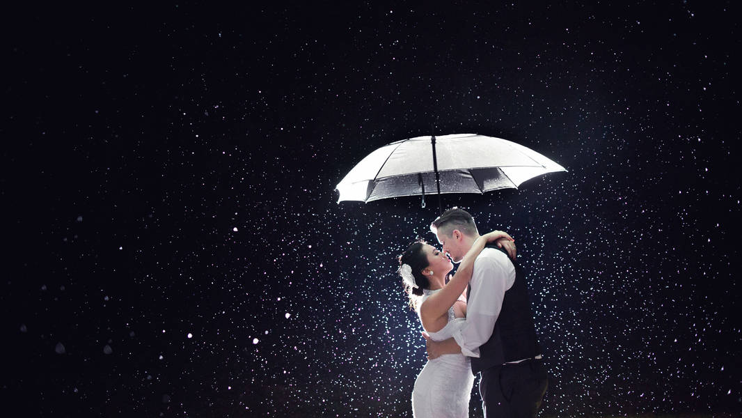 Bride and groom kissing rain thunderstorm umbrella