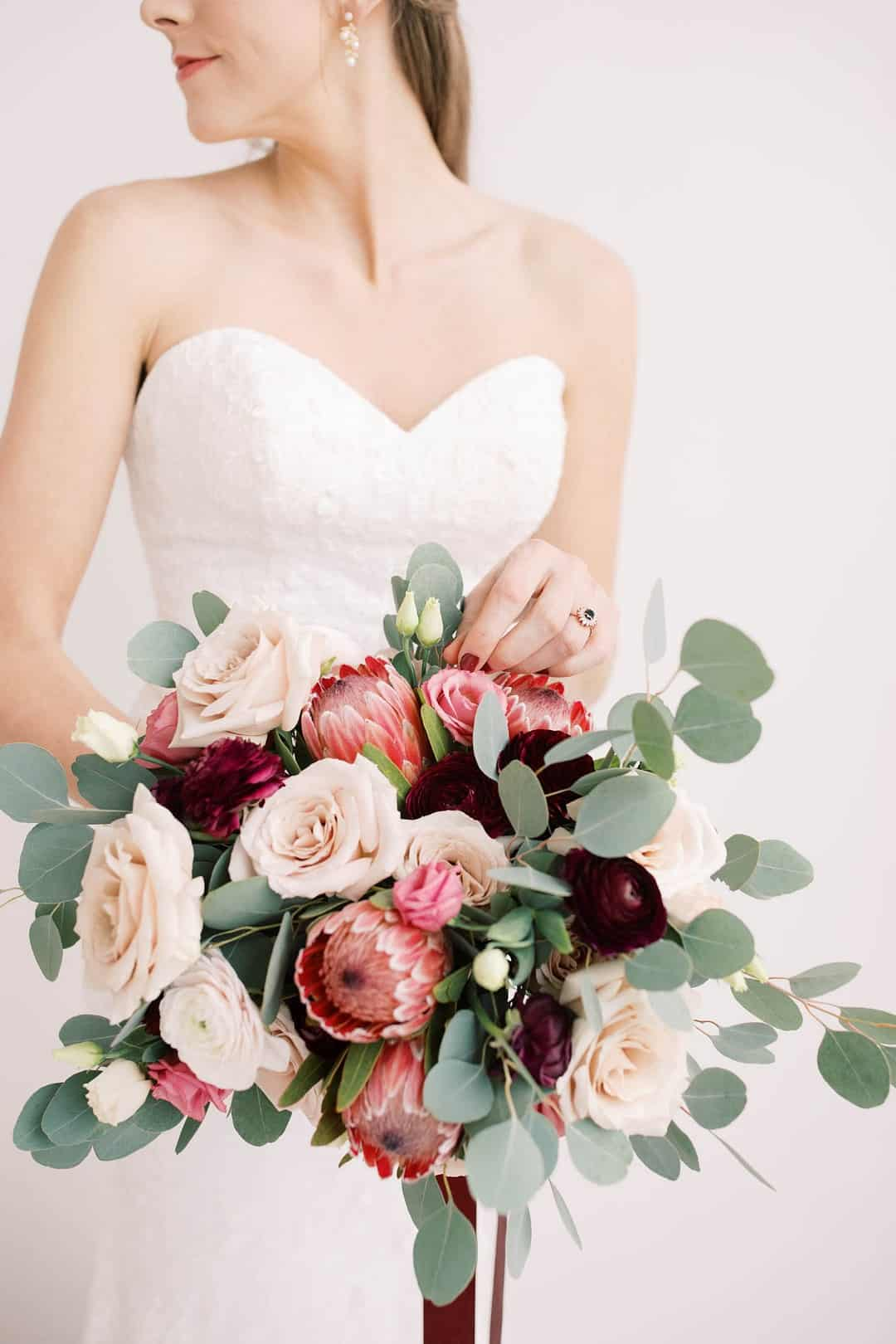 Valentines Day wedding inspiration, featuring giant heart balloon backdrop and romantic feather wedding dress