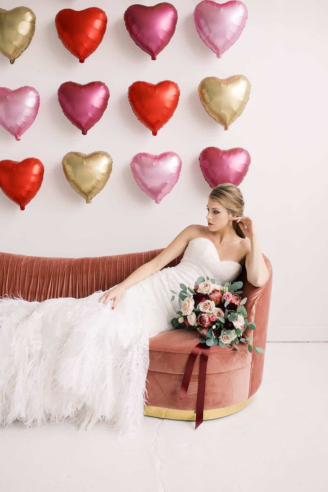 Valentines Day wedding inspiration, featuring giant heart balloon backdrop and romantic feather wedding dress.
